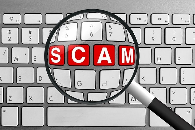 How to Avoid Affiliate Marketing Scams - Computer Keyboard with Red Scam Buttons and Magnifying Glass